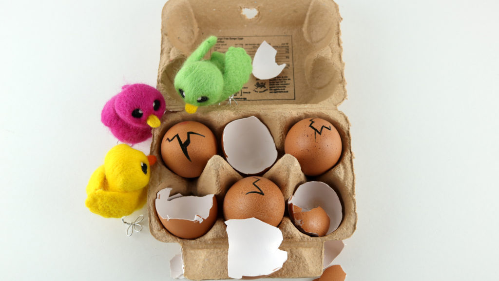 Felted chicks hatching from egg box