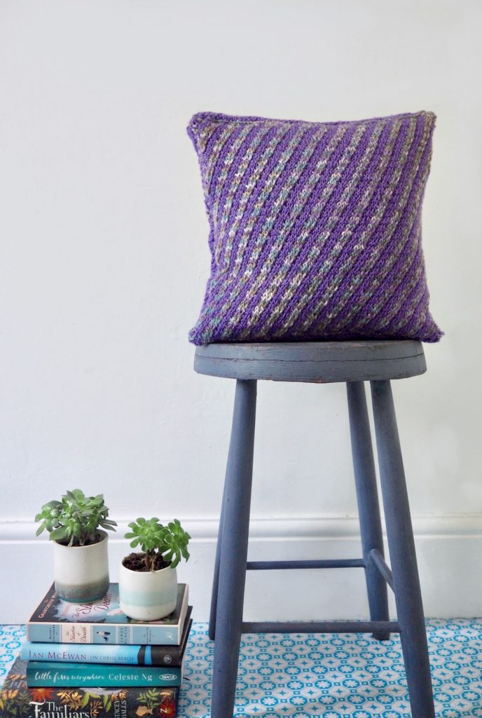 purple and grey striped cushion on blue stool