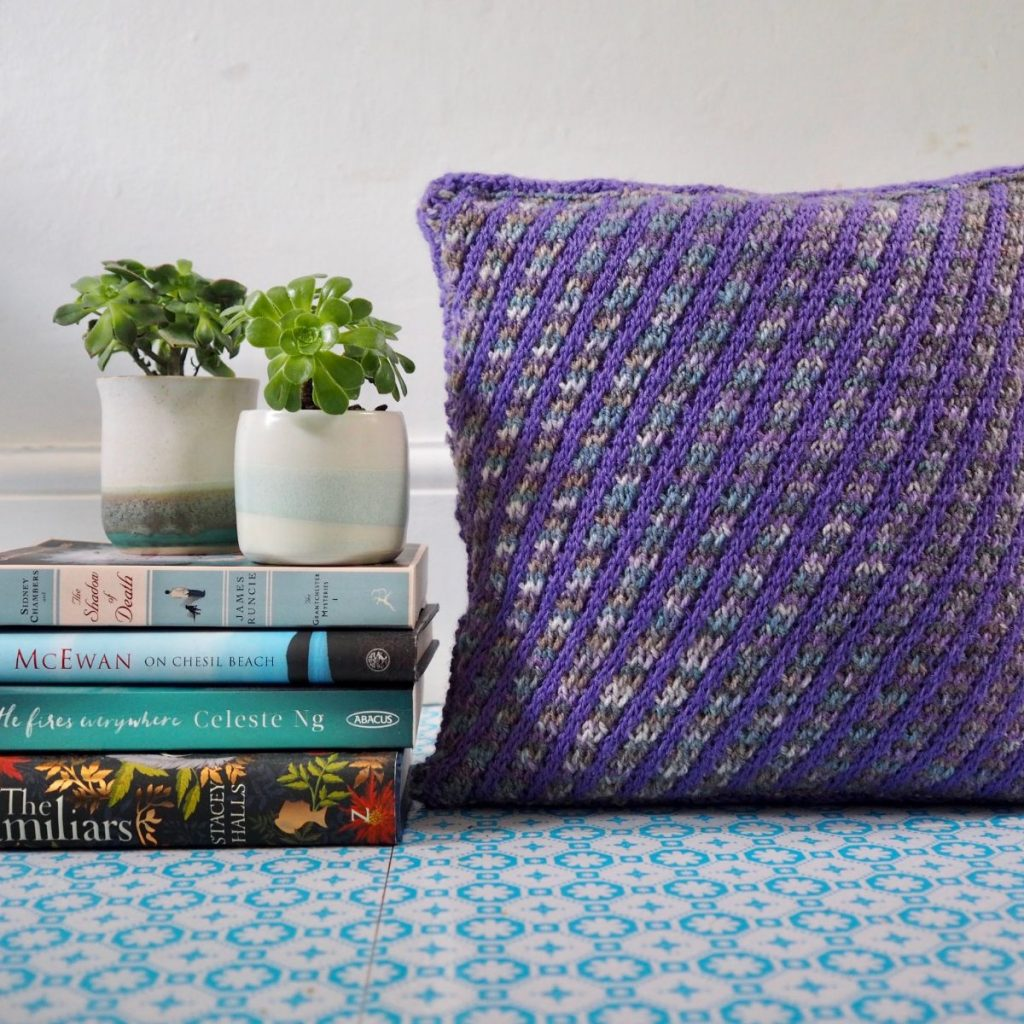 Striped purple cushion, books and ceramic vases